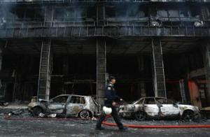 A policeman walks in front of a burnt building following riots in Athens